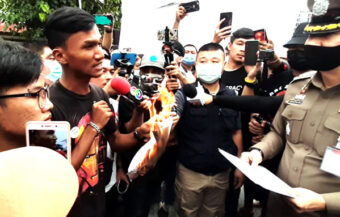 Protest leader torches legal notice to desist in front of a senior police chief at Samut Prakan rally on Sunday